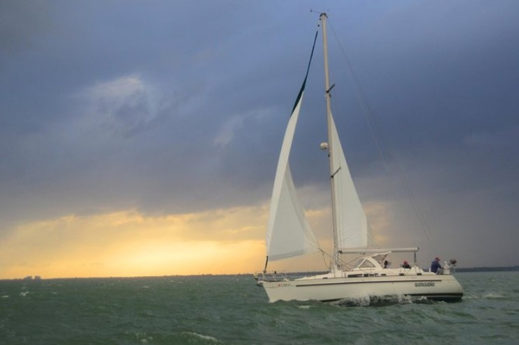 A sailboat on Biscayne Bay in Florida on a cloudy day with the setting sun in the background.