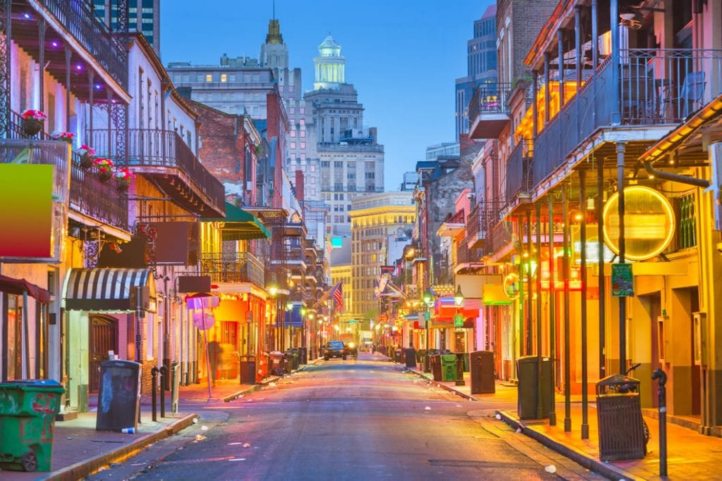 A view of a deserted and illuminated Bourbon Street in New Orleans.