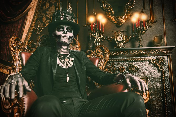 A man sits in a chair dressed in a skeleton chair.