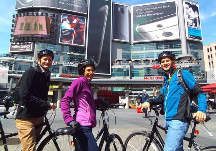 Tourists in Toronto stopping for a photo op while on a bike tour.