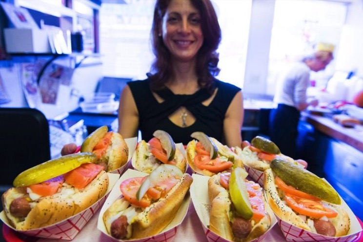 A women holds a platter of Chicago style hot dogs.