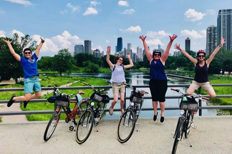 Tourists jump and celebrate while talking a bike tour in Chicago.