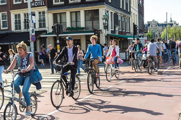 Cyclists ride through Amsterdam during a guided bike tour.