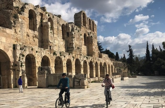 Two tourists riding their bikes near ruins in Athens, Greece.