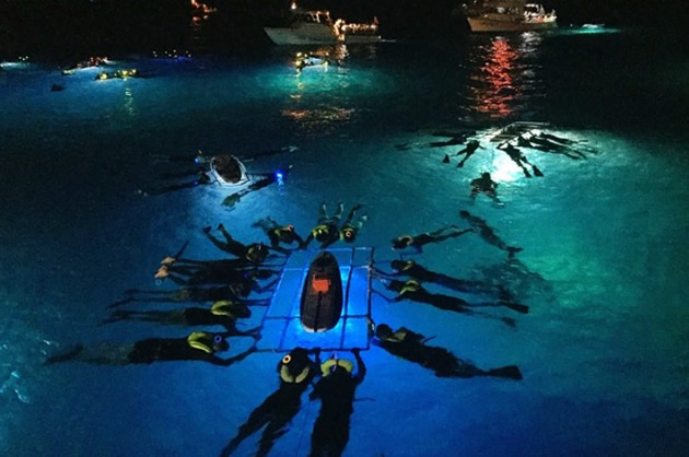 A group of tourists night snorkeling.