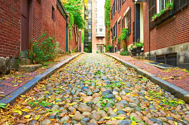 A cobblestone street in Boston surrounded by historic townhouses.