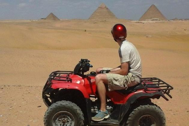 A tourist gazes at the pyramids from an ATV near Cairo, Egypt.