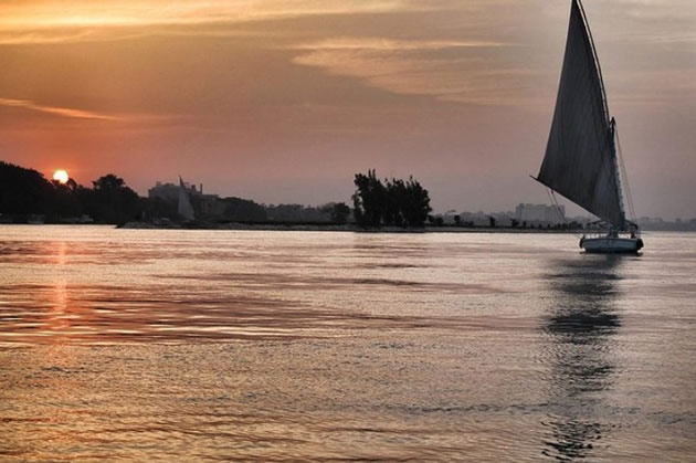 A boat on the Nile river with tourists enjoying a sunset cruise.