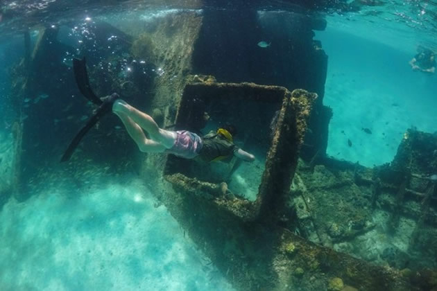 A snorkeler explores the ruins of an old boat in Cancun, Mexico.