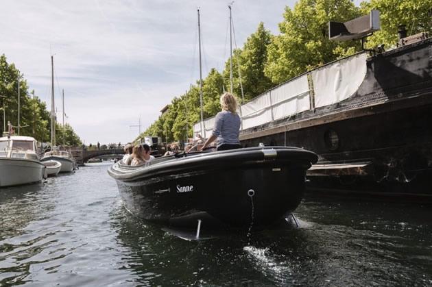 A boat tour heads down a canal in Copenhagen.