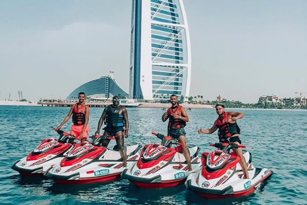Four guys posing on jet skis in Dubai.