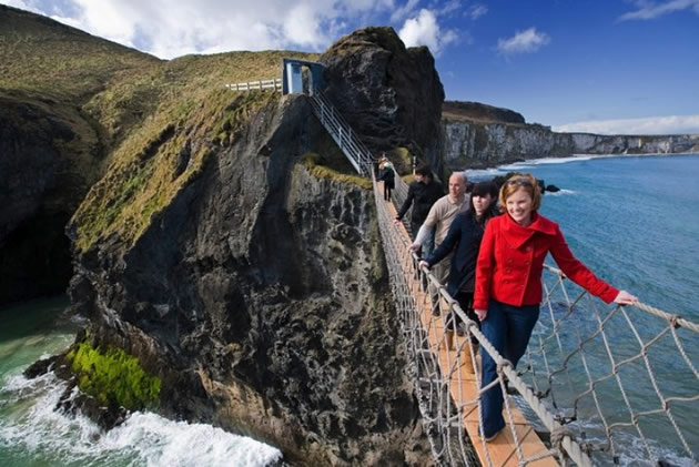 A group of tourists cross the Carrick-a-Rede rope bridge in Ireland.