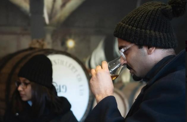 A tourist sniffs a glass of whiskey.
