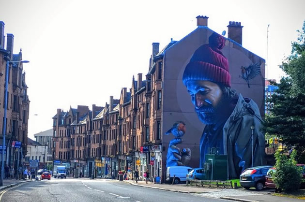 A mural featuring a man and a bird in Glasgow, Scotland.