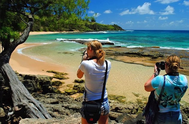 Two women taking photos of a beach on the north coast of Kauai.