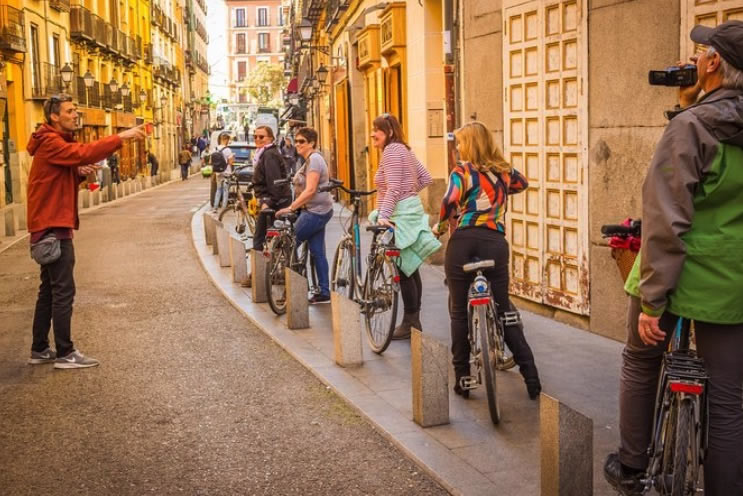 Tourists listen to their guide on a bike tour in Madrid, Spain.