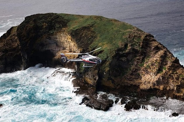 A helicopter flies over the  rugged coastline of Maui.