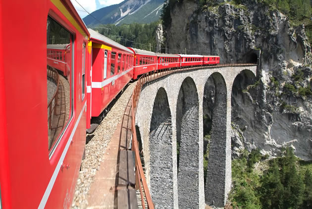 The Bernina Express crossing a very tall bridge in the Swiss Alps.