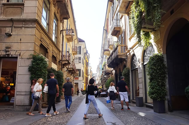 Tourists walk along a cobblestone street in the Brera district of Milan, Italy.