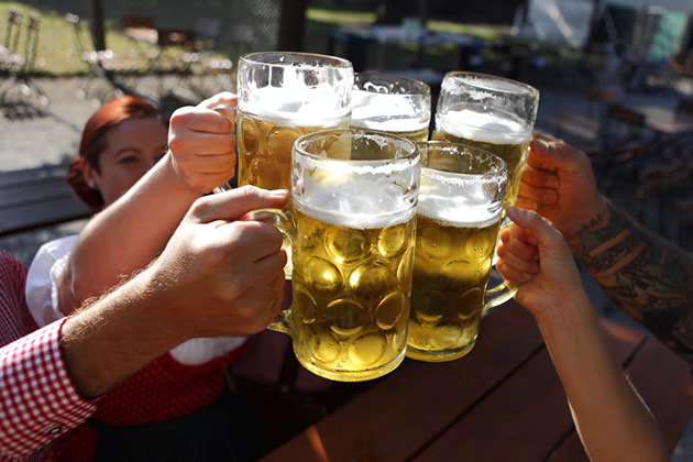 A group of people raise traditional beer glasses in Munich, Germany.