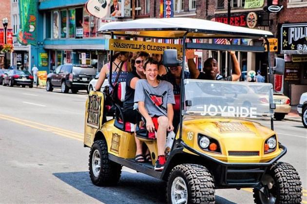 Tourists visiting Nashville via golf cart.