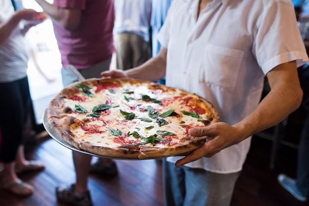 A man delivers a fresh basil and tomato pizza in Brooklyn, New York.