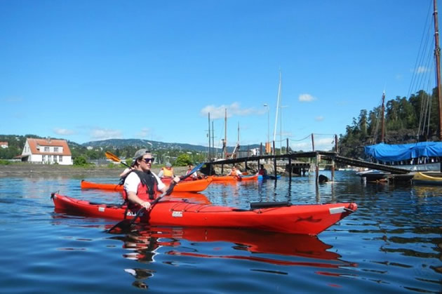 A kayaker explores a fjord in Oslofjord, Norway.