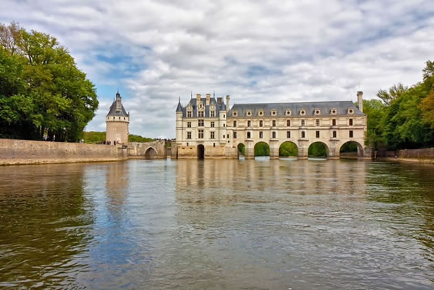 A view of Chenonceau castle from the Loire river on a partly cloudy day.