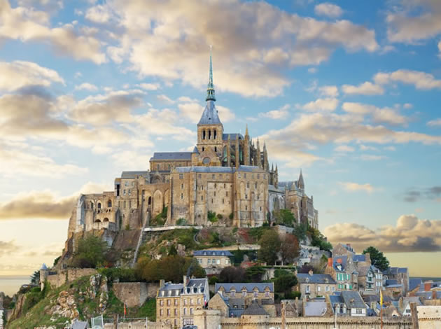 The abbey and town of Mont St. Michel against a beautiful sky at dusk.
