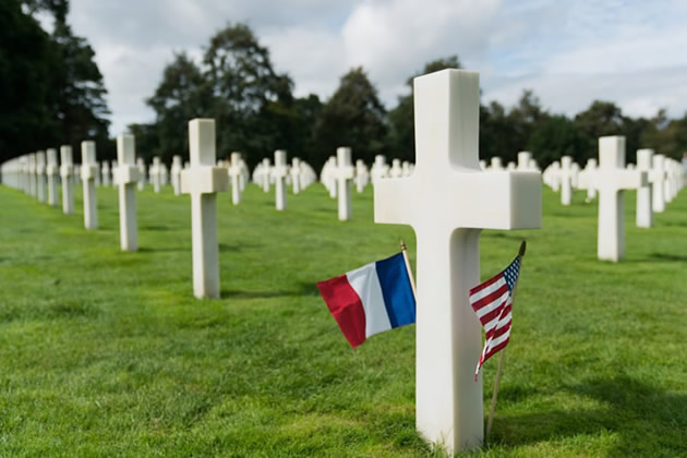 An American and French flag at the base of a gravestone at Colleville-sur-Mer in Normandy, France.