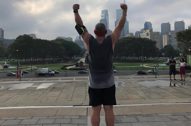 A man pretends to be Rocky Balboa on the steps in Philadelphia.