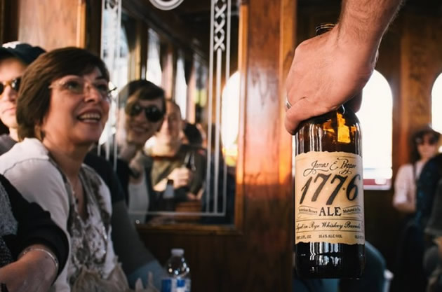 A man holding a bottle of 1776 ale on the Philadelphia party trolley.