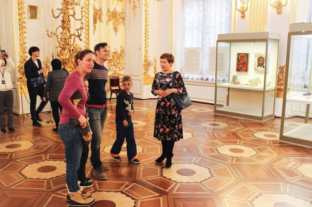 A guide leads a family through the Hermitage museum in St. Petersburg, Russia.