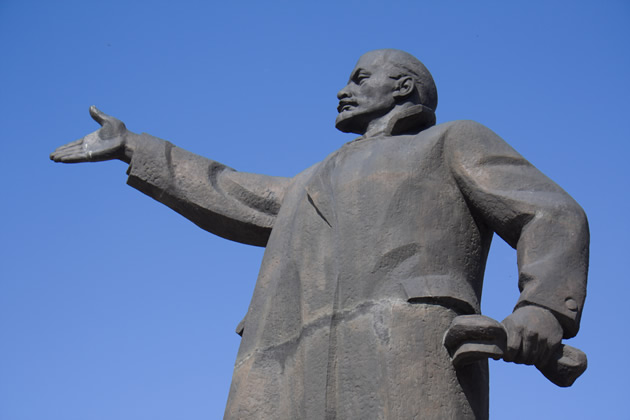 A statue of Lenin against a blue sky.