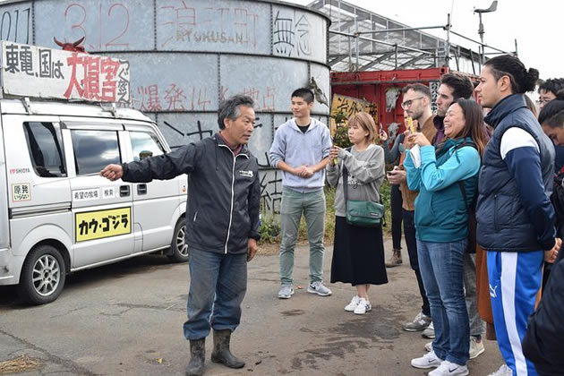 A tour guide talks to a group of tourists at the site of the Fukushima tsunami.