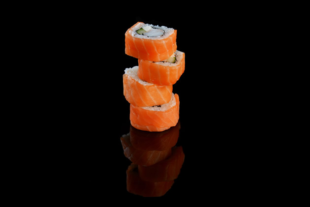 Sushi wrapped with salmon piled up like tires against a black background.