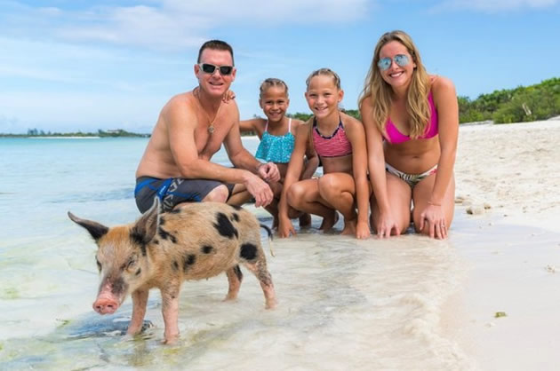 A family on a beach poses for a photo next to one of the famous swimming pigs in the Bahamas.