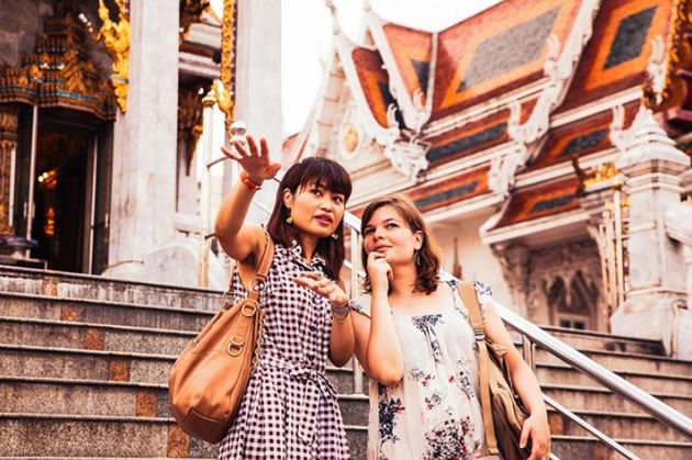 A tour guide discusses a buildings architecture in Bangkok.