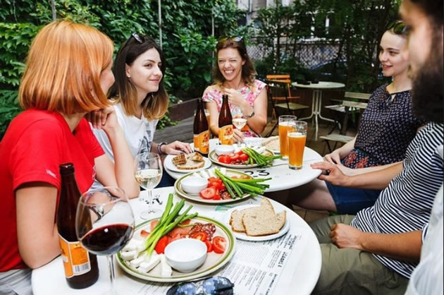 Tourists enjoy food tastes at a restaurant in Bucharest, Romania.