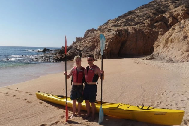 A pair of kayakers standing on shore in Cabo San Lucas, Mexico.