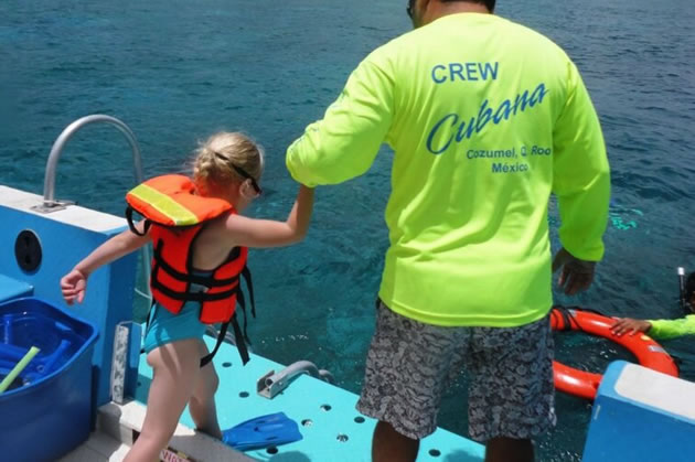 A guide helps a young visitor off of a diving boat in Cozumel.