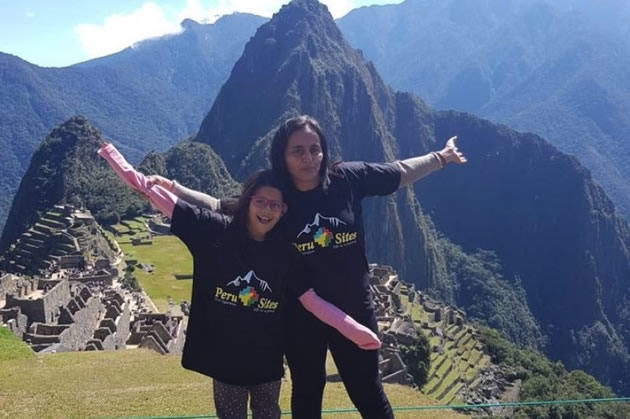 A mom and her daughter pose in front of Machu Picchu.