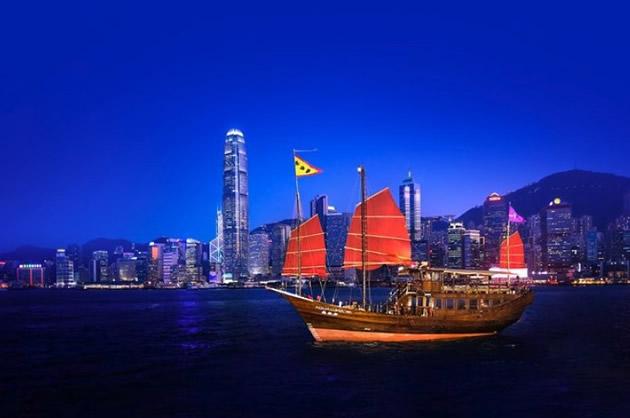 Junk-style schooner sails in Hong Kong harbor by night.