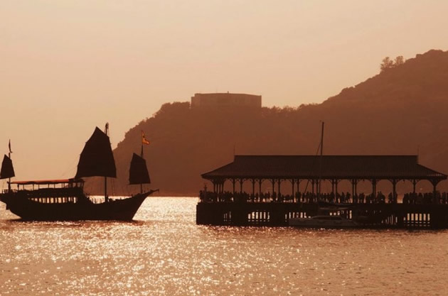 Silhouette of a classic Chinese junk in Hong Kong harbor.