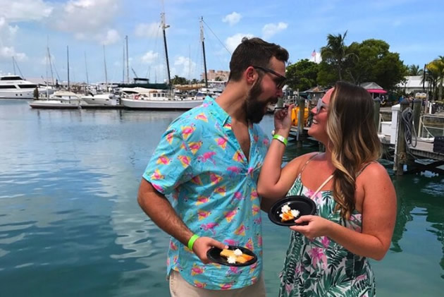 Young woman feeds her friend seafood bites along Key West harbor.