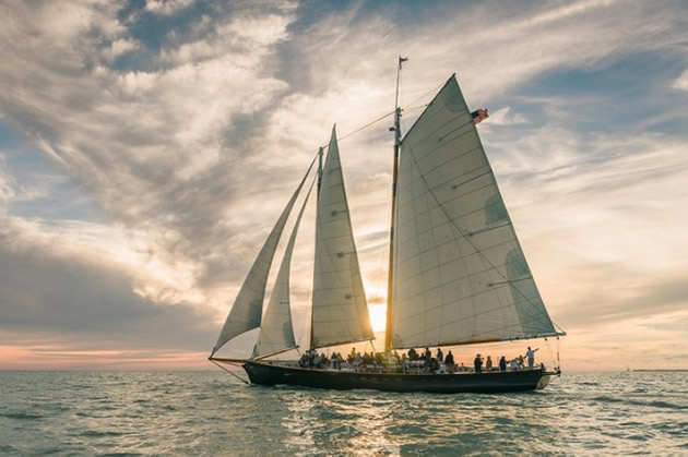 Four sail schooner silhouetted against a setting sun in Key West.