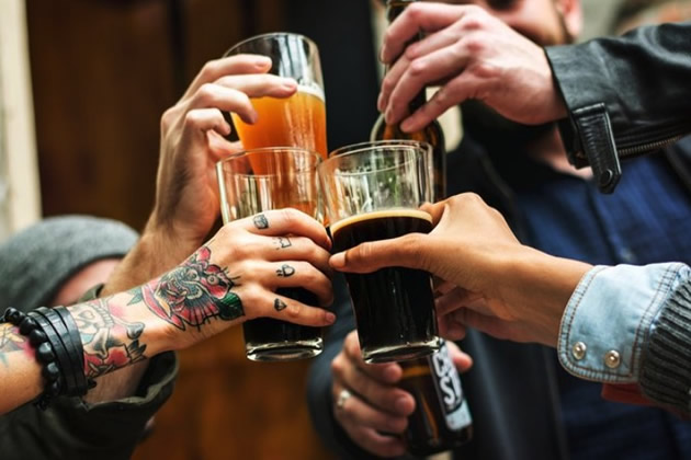 Tattooed hand toasts friends with Kiev specialty beer.
