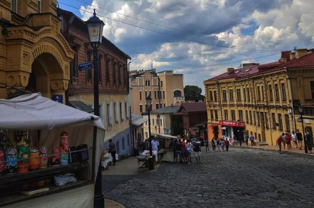 Vintage street lamp anchors a Kiev cobblestone market street.