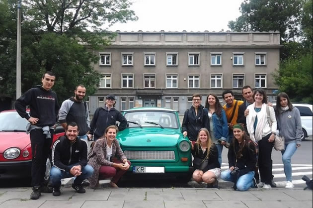 Tourists pose beside a Soviet-era car as they tour Krakow.