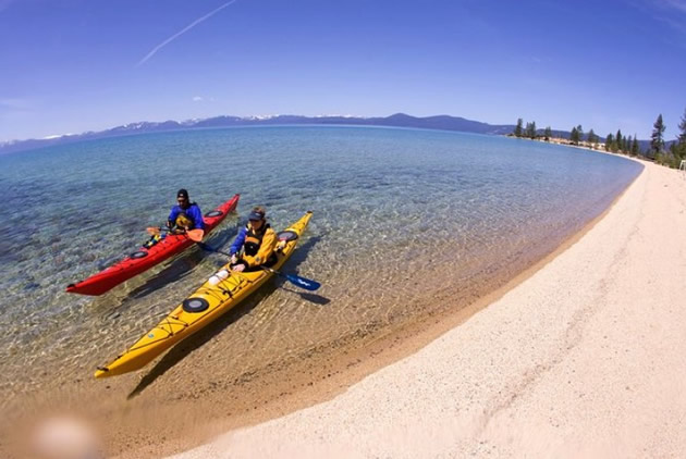 Kayakers paddle in red and blue kayaks on a sandy shore of Lake Tahoe.